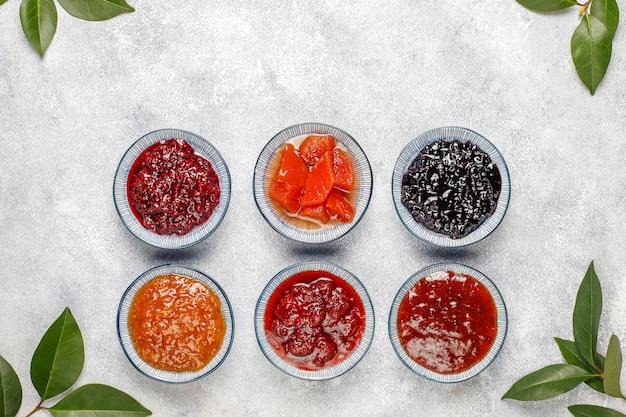 Surtido de mermeladas dulces y frutas y bayas de temporada, vista superior