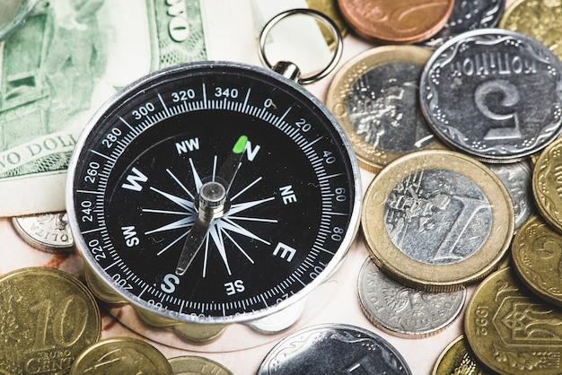 Surtido de monedas y brújula para viajar
