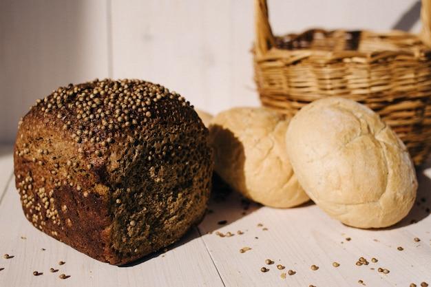 Surtido de pan horneado en el fondo blanco de la mesa de madera, luz dura