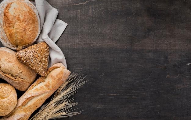 Surtido de pan horneado sobre tela con trigo