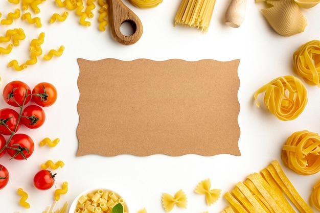 Surtido de pasta cruda y tomates con maqueta de cartón