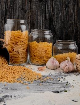 Surtido de pasta italiana cruda en frascos de vidrio con ajo sobre la mesa con harina
