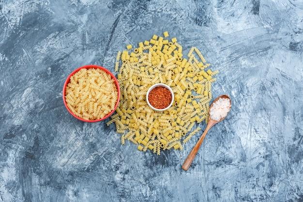 Surtido de pasta en un recipiente con sal en una cuchara de madera, hojuelas de pimienta plana yacía sobre un fondo de yeso sucio