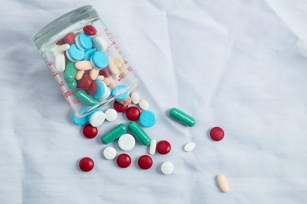 Surtido de pastillas de medicina farmacéutica, tabletas y cápsulas y botella de gress