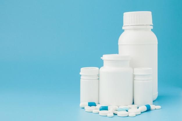 Surtido de píldoras de medicina farmacéutica tabletas y cápsulas y botella sobre fondo azul.