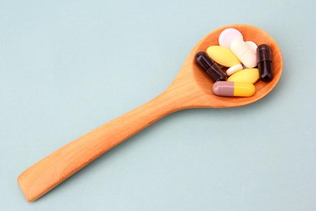 Surtido de píldoras de medicina farmacéutica, tabletas y cápsulas en la cuchara de madera.