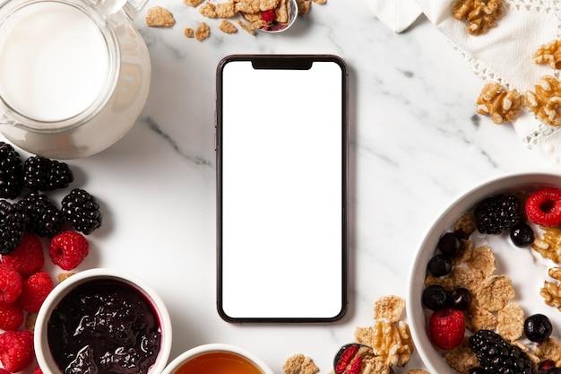 Surtido plano de cereales de tazón saludable con teléfono inteligente de pantalla vacía