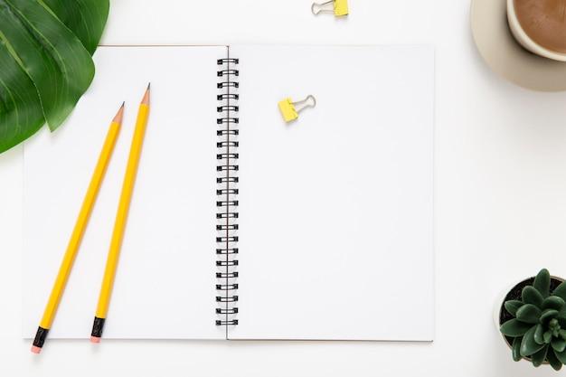 Surtido plano de elementos de escritorio con cuaderno abierto