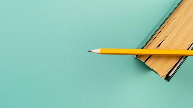 Surtido plano con lápiz sobre un libro