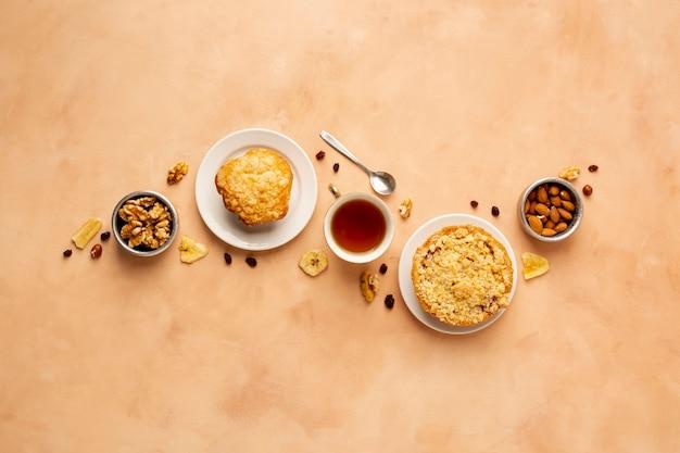 Surtido plano con magdalenas y té.