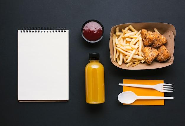 Surtido plano con papas fritas y cuaderno