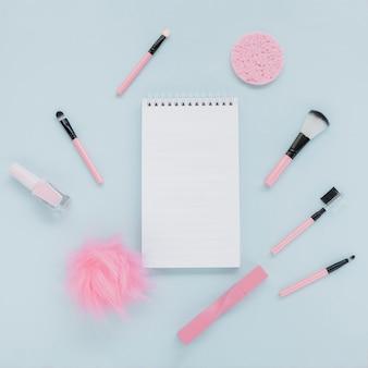 Surtido plano con pinceles de maquillaje y cuaderno
