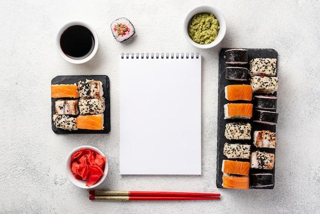 Surtido plano de rollos de sushi maki surtido con cuaderno en blanco