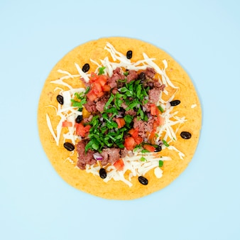 Surtido plano con sabrosa comida mexicana sobre fondo azul.