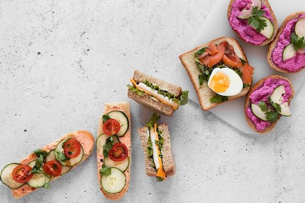Surtido plano de sándwiches frescos sobre fondo de cemento