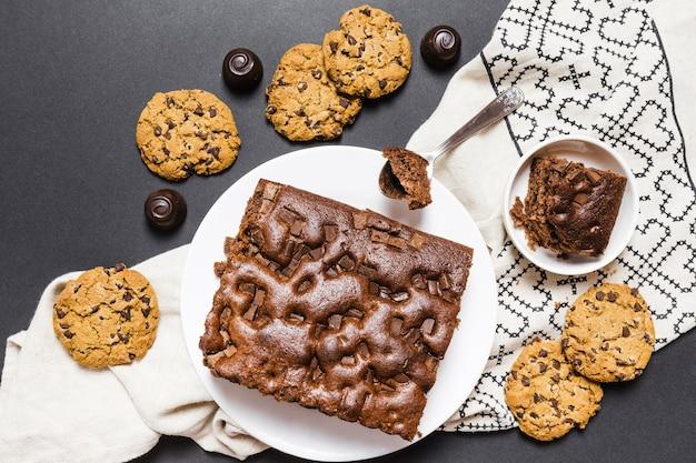 Surtido plano con tarta de chocolate y galletas.