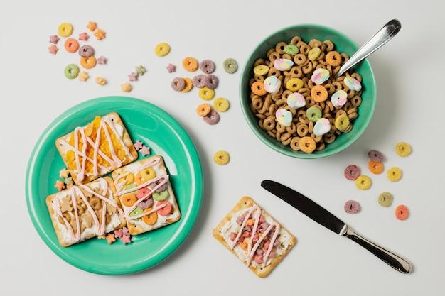Surtido plano con tazón de cereal y tartas en un plato