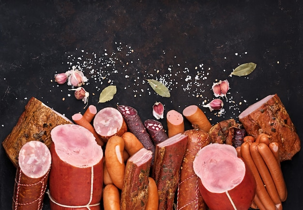 Surtido de productos cárnicos, incluyendo salchichas, tocino, jamón, especias, ajo en una mesa negra vista desde la parte superior