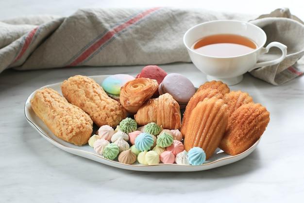 Surtido de productos horneados dulces / pastelería con espacio de copia en el centro de la mesa de madera para texto o receta. macarrones, merengue, magdalena, eclair craquelin, mini croissant, galletas grandes. vista superior