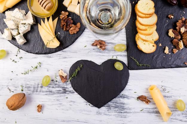 Surtido de queso con nueces, pan y miel en placa de pizarra de piedra