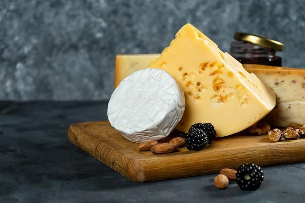 Surtido de queso sobre un fondo de piedra oscura con espacio de copia. diferentes tipos: camembert, queso con especias, queso holandés en tabla de cortar de madera. almendras, moras y mermelada con queso. enfoque suave