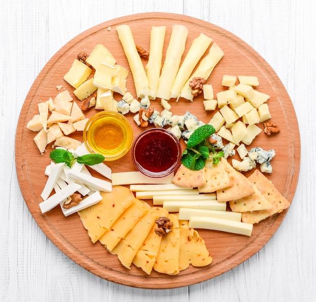 Surtido de queso sobre pizarra negra, nueces y miel, decorado con uvas y hojas de menta.