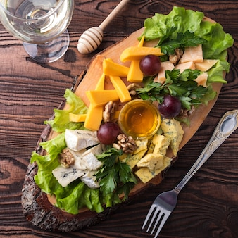 Surtido de quesos en tablero de madera uva y nueces. de cerca. vista superior