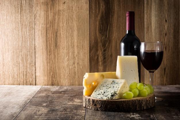 Surtido de quesos y vinos en mesa de madera. copyspace