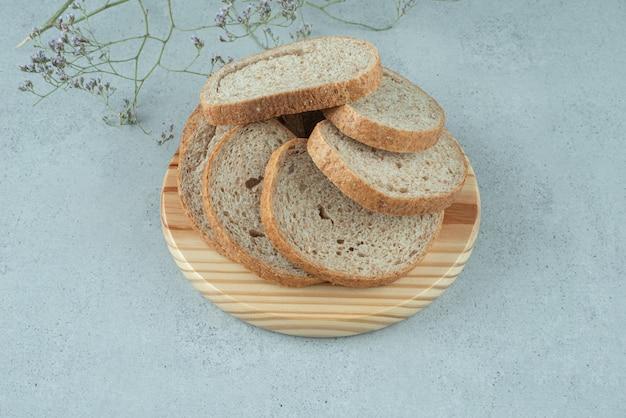 Surtido de rebanadas de pan en placa de madera