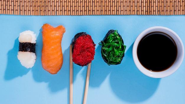 Surtido de rollos de sushi con salsa de soja en la mesa