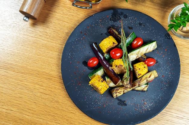 Surtido de sabrosas verduras a la plancha sobre placa de piedra negra. frito fresco y eco maíz, berenjenas, tomates, romero, calabacín vista superior.
