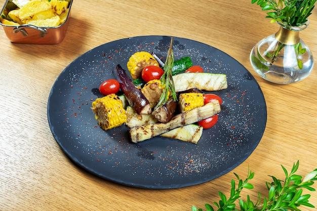 Surtido de sabrosas verduras a la plancha sobre placa de piedra negra. maíz fresco y ecológico frito, berenjenas, tomates, romero, calabacín. plana pone comida.