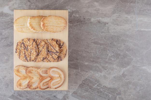 Surtido de snacks con diferentes galletas en una pequeña tabla de mármol