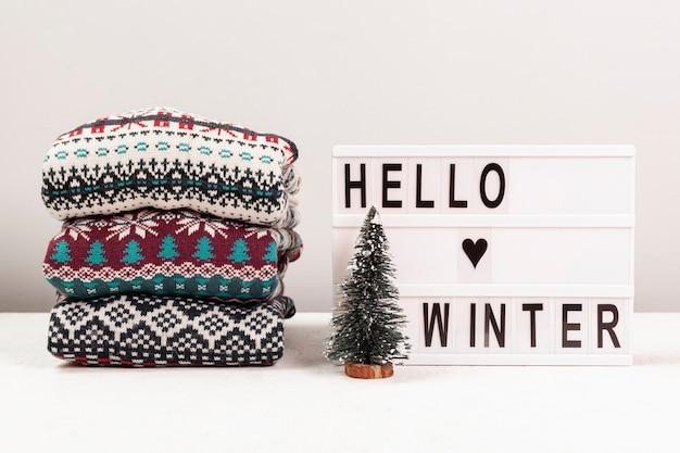 Surtido con suéteres y hola cartel de invierno