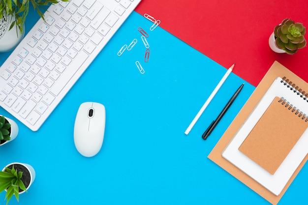 Surtido de suministros de oficina y accesorios tecnológicos, mesa de trabajo moderna, vista superior