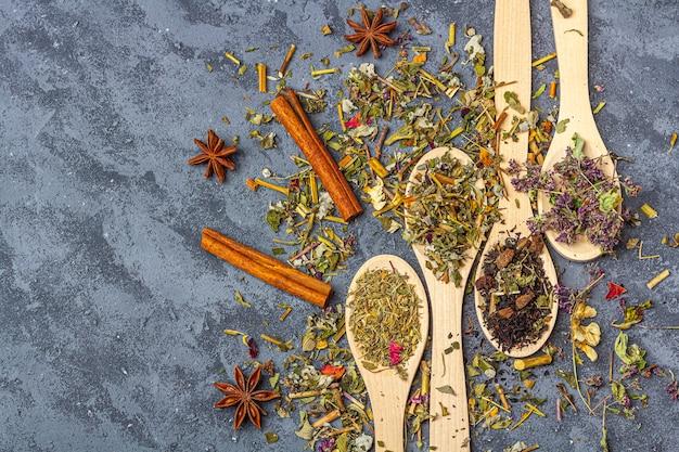 Surtido de té diferente en cucharas de madera con anís y canela en estilo rústico. té orgánico a base de hierbas, verde y negro con pétalos de flores secas para la ceremonia del té.
