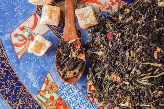 Surtido de té seco en cucharas, sobre superficie de madera.