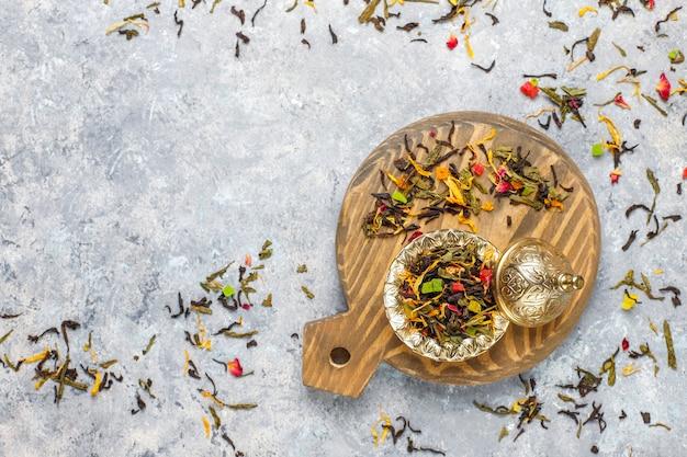 Surtido de té seco en mini platos dorados vintage. tipos de té