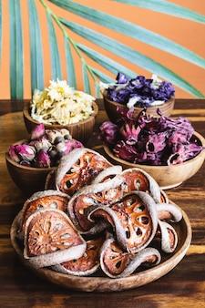 Surtido de té tropical saludable a base de hierbas secas en tazones de madera y hojas de palma sobre fondo rústico.
