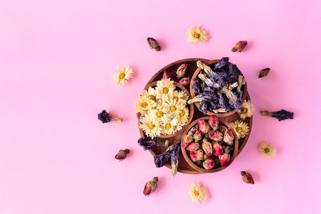 Surtido de té tropical saludable a base de hierbas secas en tazones de madera sobre fondo rosa.