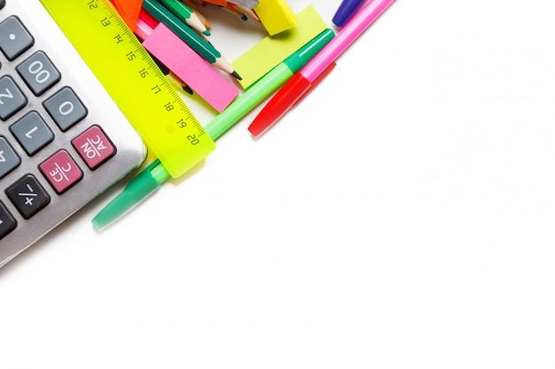 Surtido de útiles escolares, incluidos bolígrafos, lápices, tijeras, pegamento y una regla, sobre un fondo blanco.