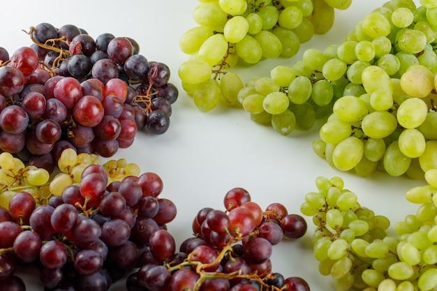 Surtido de uvas en blanco, vista de ángulo alto.