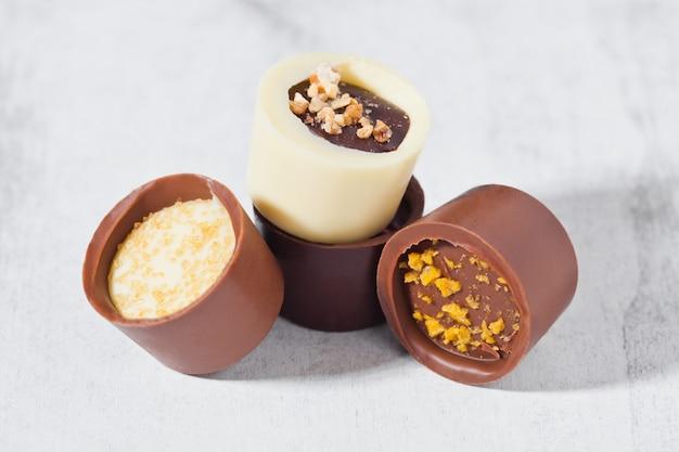 Surtido de variedad de caramelos de chocolate blanco y negro de lujo sobre fondo blanco con sombras duras