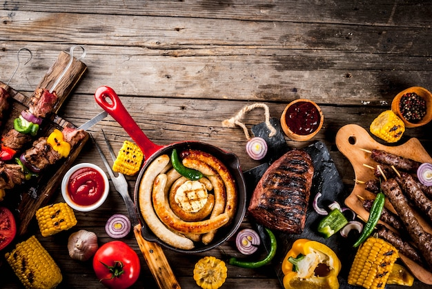 Surtido de varios alimentos a la parrilla, carne a la parrilla, fiesta de barbacoa - shish kebab, salchichas, filete de carne a la parrilla, verduras frescas, salsas