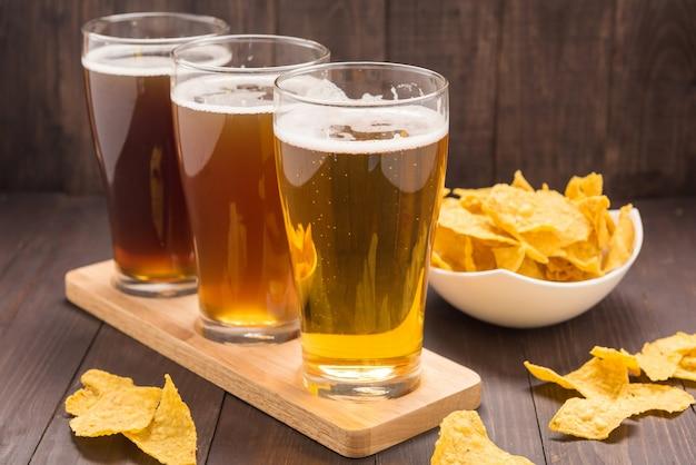 Surtido de vasos de cerveza con nachos chips en una mesa de madera.