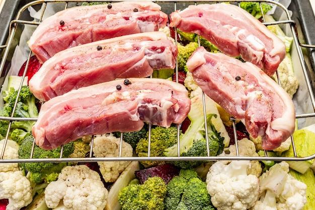Surtido de verduras frescas en una bandeja para hornear. carne de panceta cruda a la parrilla