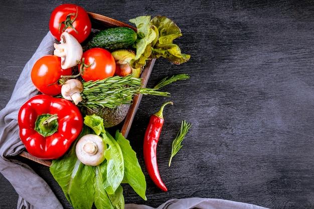 Surtido de verduras frescas en una caja de madera, espacio libre para texto.
