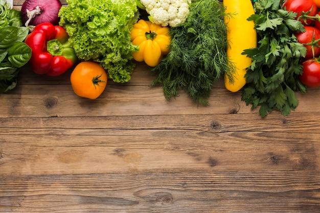 Surtido de verduras laico plano sobre fondo de madera