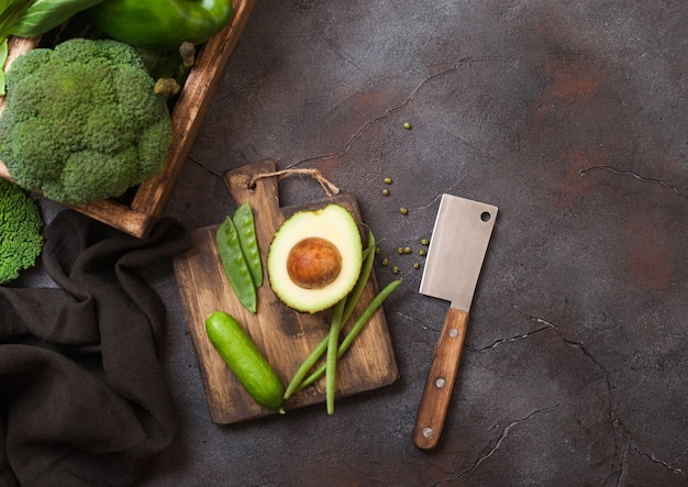 Surtido de verduras orgánicas crudas en tonos verdes en caja de madera sobre la superficie de piedra oscura