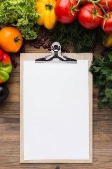 Surtido de verduras vista superior con portapapeles vacío